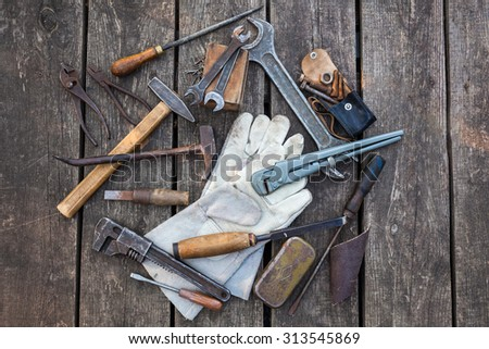 Working tools, leather glove on a grunge wooden background - stock photo