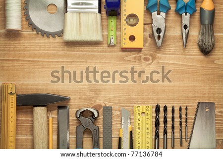Working tools on a wooden boards background. Including saw, ruler, drill, nails, pliers,hammer, brush,thread,chisel and other. - stock photo