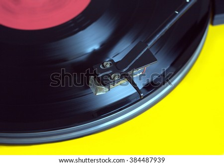 Working vinyl LP record with red label sound reproduction on vintage turntable record player with yellow case. Horizontal from above photo closeup - stock photo