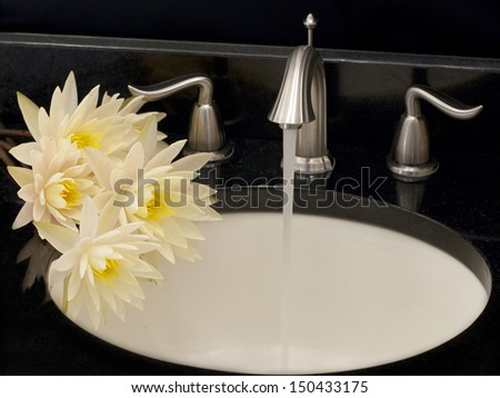 Working water tap and a few lotuses over sink - stock photo