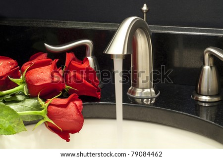 Working water tap and a few red roses on a sink. - stock photo