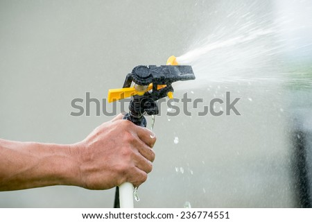 Working watering garden from hose,   - stock photo