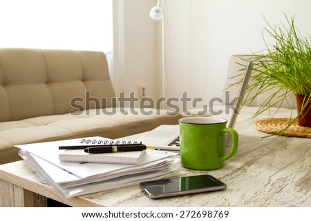 Working with a pile of papers and a laptop