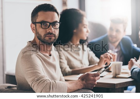 Working with his business team. Young handsome man looking at camera while sitting at the office table on business meeting with his coworkers - stock photo