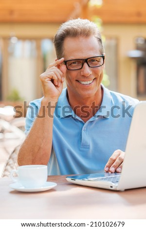 Working with pleasure. Cheerful mature man working at laptop and smiling while sitting at the table outdoors with house in the background  - stock photo