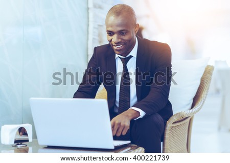 Working with pleasure. Cheerful young African businessman using his laptop while sitting at the restaurant - stock photo