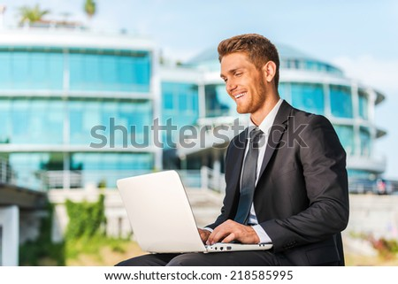 Working with pleasure. Handsome young man in formalwear working on laptop and smiling while sitting outdoors and against building structure - stock photo