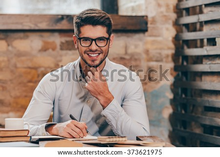 Working with pleasure. Handsome young man in glasses making some notes in his note pad and looking at camera with smile while sitting at his working place - stock photo