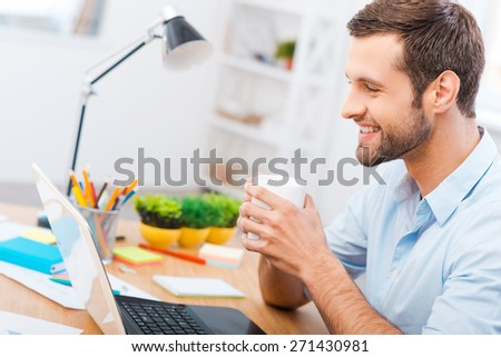Working with pleasure. Handsome young man in shirt holding a cup of coffee and smiling while sitting at his working place - stock photo