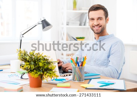 Working with pleasure. Handsome young man in shirt working on laptop and smiling at camera while sitting at his working place - stock photo