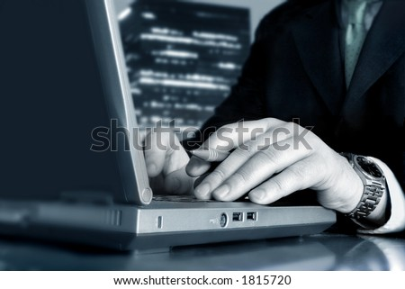 Working with the laptop and a skyscraper in the background - stock photo
