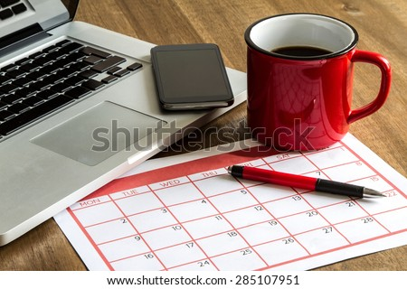 Working with the laptop and organizing monthly activities and appointments in the calendar - stock photo