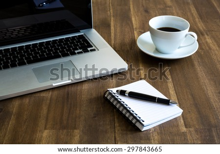Working with the laptop, taking notes and drinking a coffee - stock photo