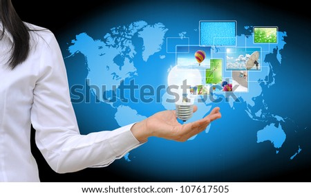 working women hand holding light bulb and streaming images virtual buttons - stock photo