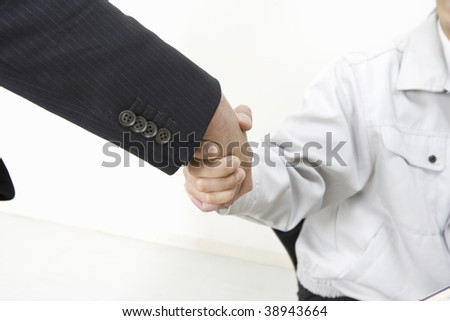 Workman and businessman shaking hands happily