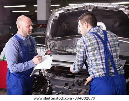 Workman calculating the price of work at auto repair workshop