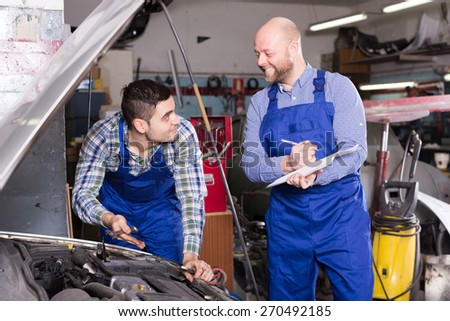 Workman calculating the price of work at the auto repair shop  - stock photo
