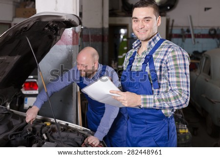 Workman calculating the price of work in the auto repair shop  - stock photo
