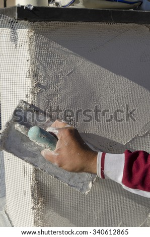 workman during the laying of a reinforcing mesh for plaster