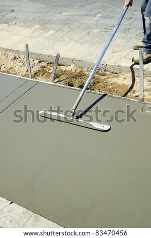 Workman finishes and smooths concrete surface on new sidewalk - stock photo