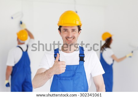 workman gives thumbs up in front of two painters - stock photo