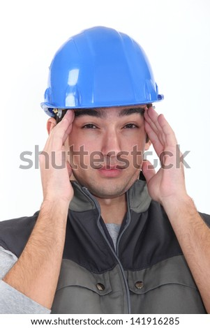 workman having migraine - stock photo