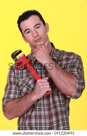 Workman holding a pipe wrench - stock photo