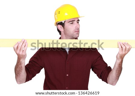 Workman holding a plank - stock photo
