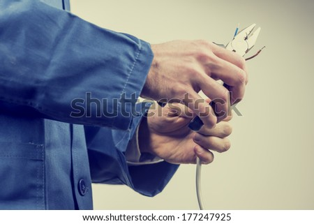 Workman in overalls repairing an electric cable or wiring using pliers while doing a domestic or industrial installation , maintenance or repairs, close up of his hands. With retro filter effect. - stock photo