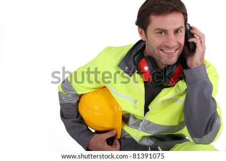 Workman in protective gear with mobile phone - stock photo