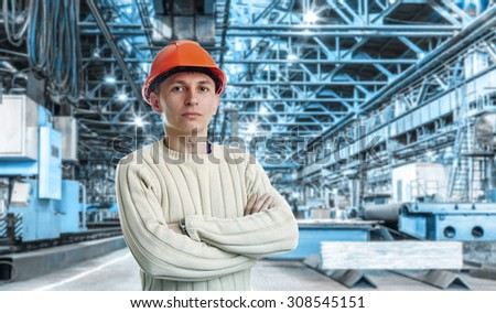Workman in red helmet in the workshop of machinery plant