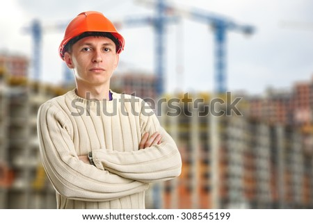 Workman in red helmet on background of buildings under construction and cranes - stock photo
