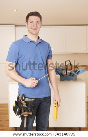 Workman Installing Fitted Kitchen - stock photo