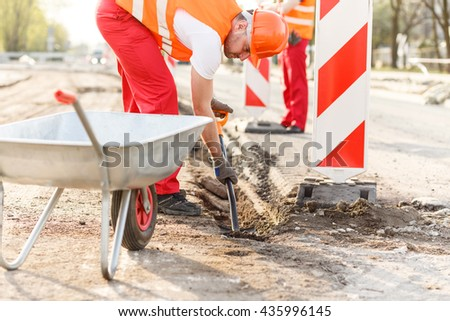 Workman loading a wheelbaroow on the construction site - stock photo
