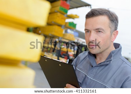Workman looking closely at stack of wood - stock photo