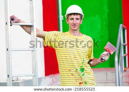 workman male painter with paintbrush and stepladder during decorating construction works  house facade - stock photo