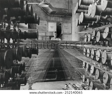 Workman operating an industrial loom strung with hundreds of wool threads. Chicago's Olsen Rug Company. Ca. 1950. 13_232) - stock photo