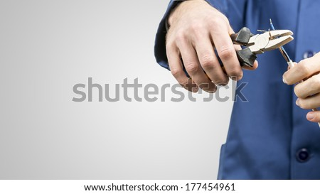 Workman or electrician repairing an electrical cable with a pair of pliers to restore supply to the house, close up view of his hands in blue overalls on grey with copyspace - stock photo