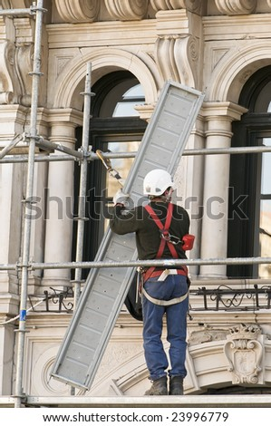 Workman putting up scaffolding - stock photo