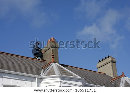 Workman repairing a chimney stack on a roof - stock photo