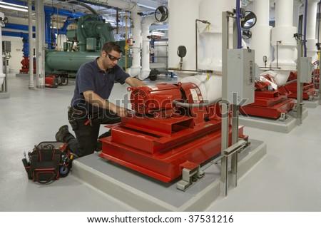 workman repairing electric motor in building transformer underground - stock photo