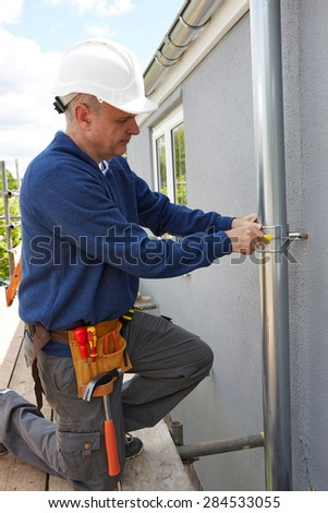 Workman Replacing Guttering On Exterior Of House - stock photo