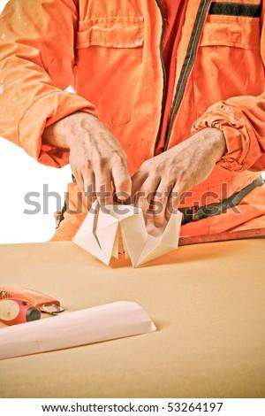 workman's hands make a paper ship - stock photo