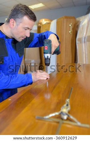 Workman screwing down the lid of a coffin