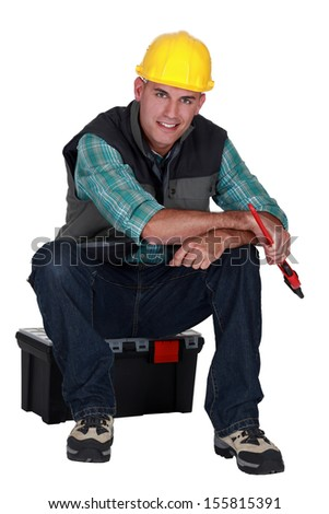 Workman sitting on a toolbox - stock photo