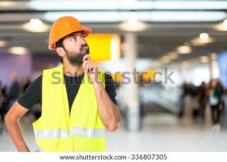 Workman thinking on unfocused background - stock photo