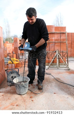 Workman using a cement paddle whisk - stock photo