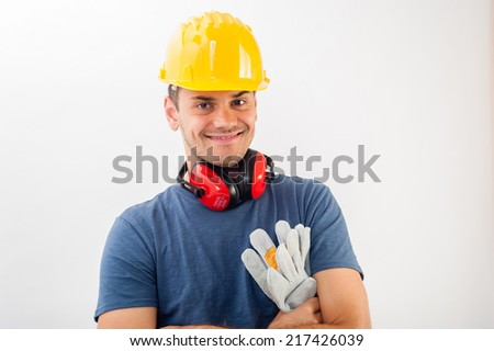 Workman wearing a yellow  hard hat and full protective gear smiling at the camera with his arms crossed. Isolated over white in horizontal format.
