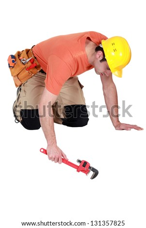 Workman with an adjustable wrench - stock photo
