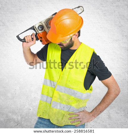 Workman with chainsaw over textured background